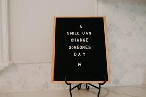 A smile can change someones day writing on a sign