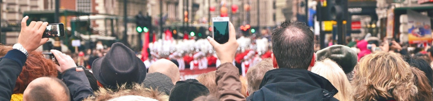 Women holding her phone capturing a parade
