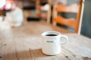 Mug on desk with the word Begin-1