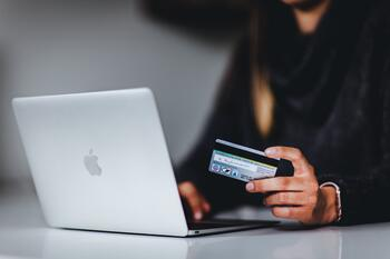 hand holding a credit card and a laptop