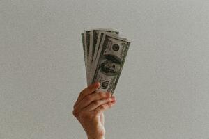 hand holding up money in the air