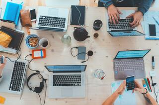 Laptops, phones and headphones on a desk